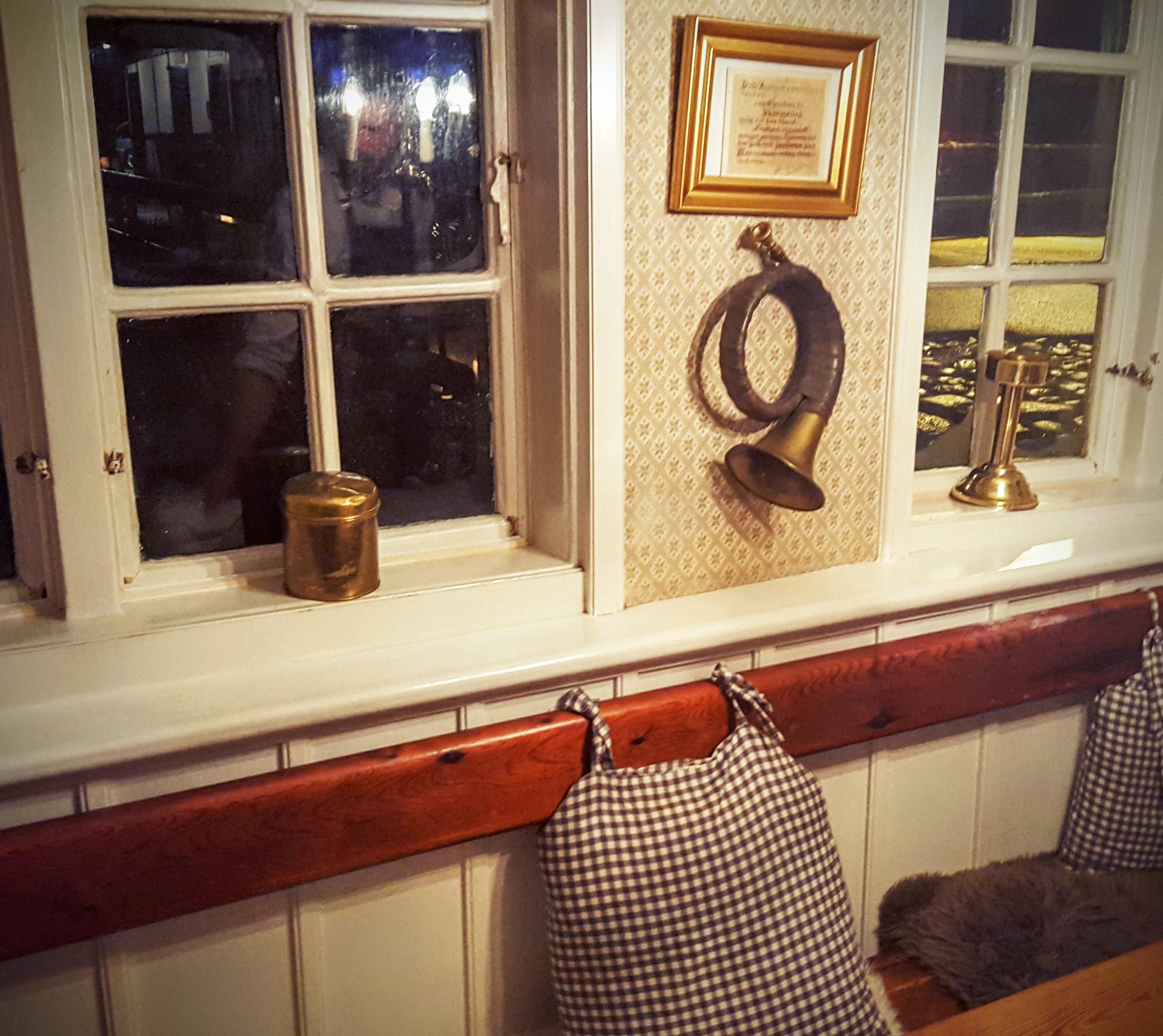 Træbænk med puder og rustikke genstande i vindueskarmen Restaurant Skovmøllen