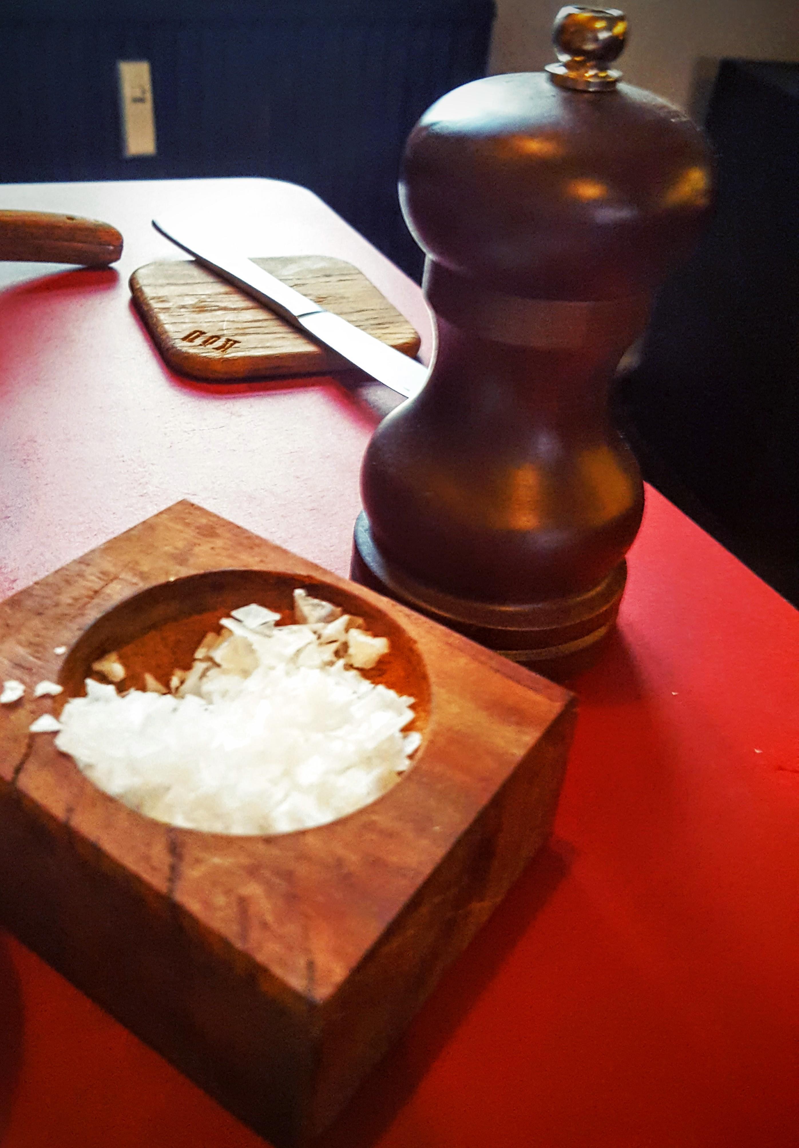 Köd brød skærebræt, træskål med salt flager og peberkværn