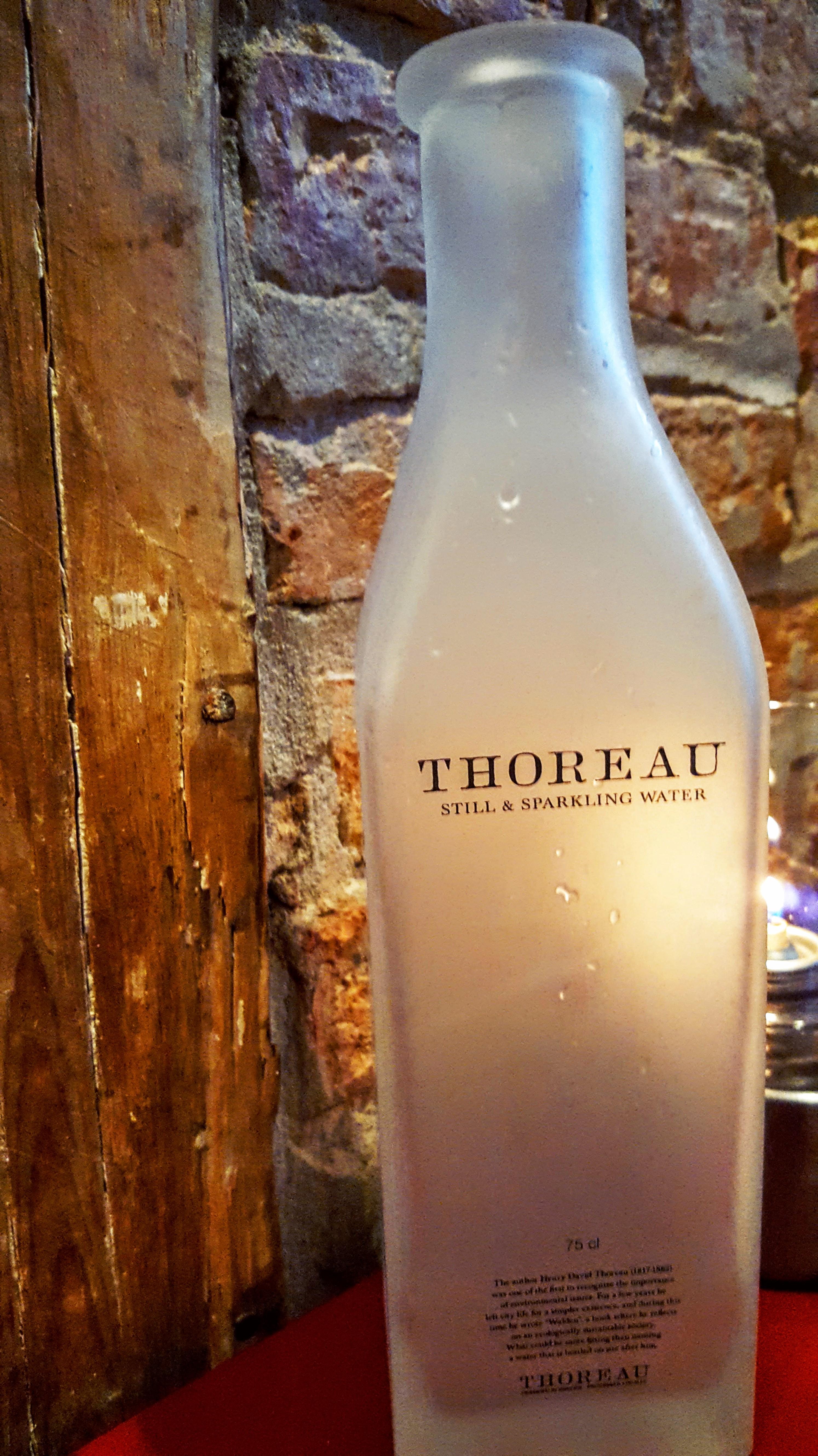 Thoreau danskvand flaske; mursten og træ væg; stearinlys